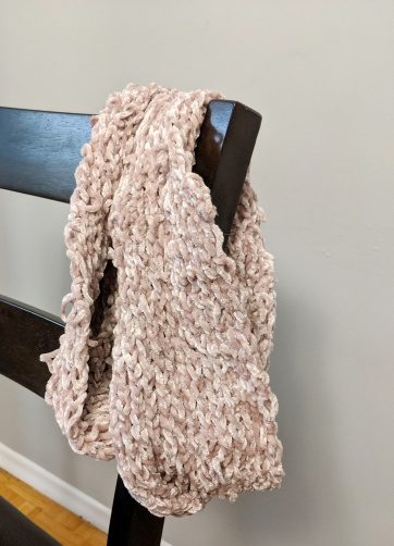 A ribbed velvet scarf hangs over the back of chair
