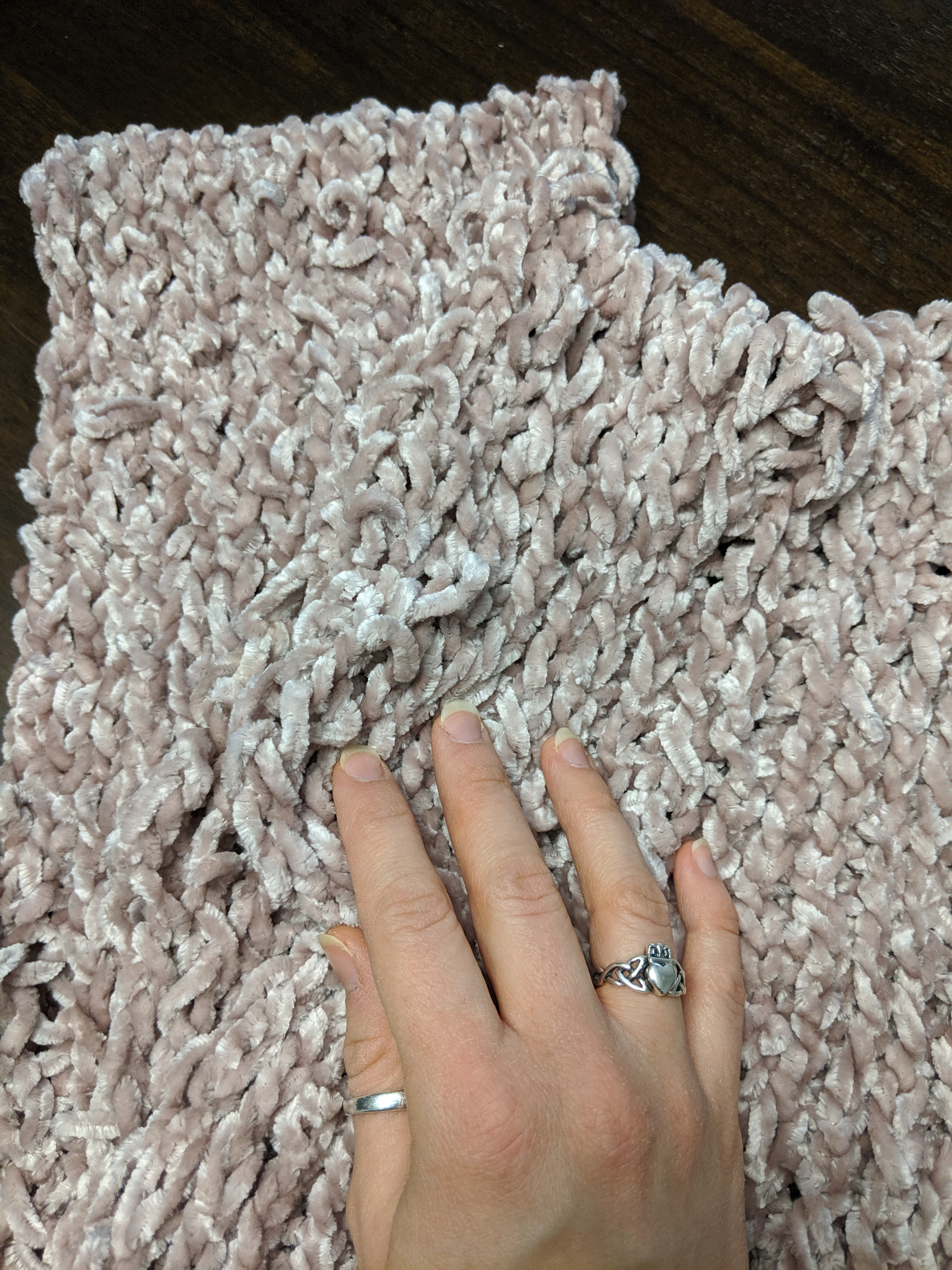A hand caresses a ribbed infinity scarf made of velvet yarn