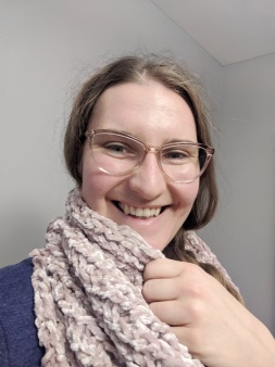 Young white woman wearing a blush pink knit infinity scarf