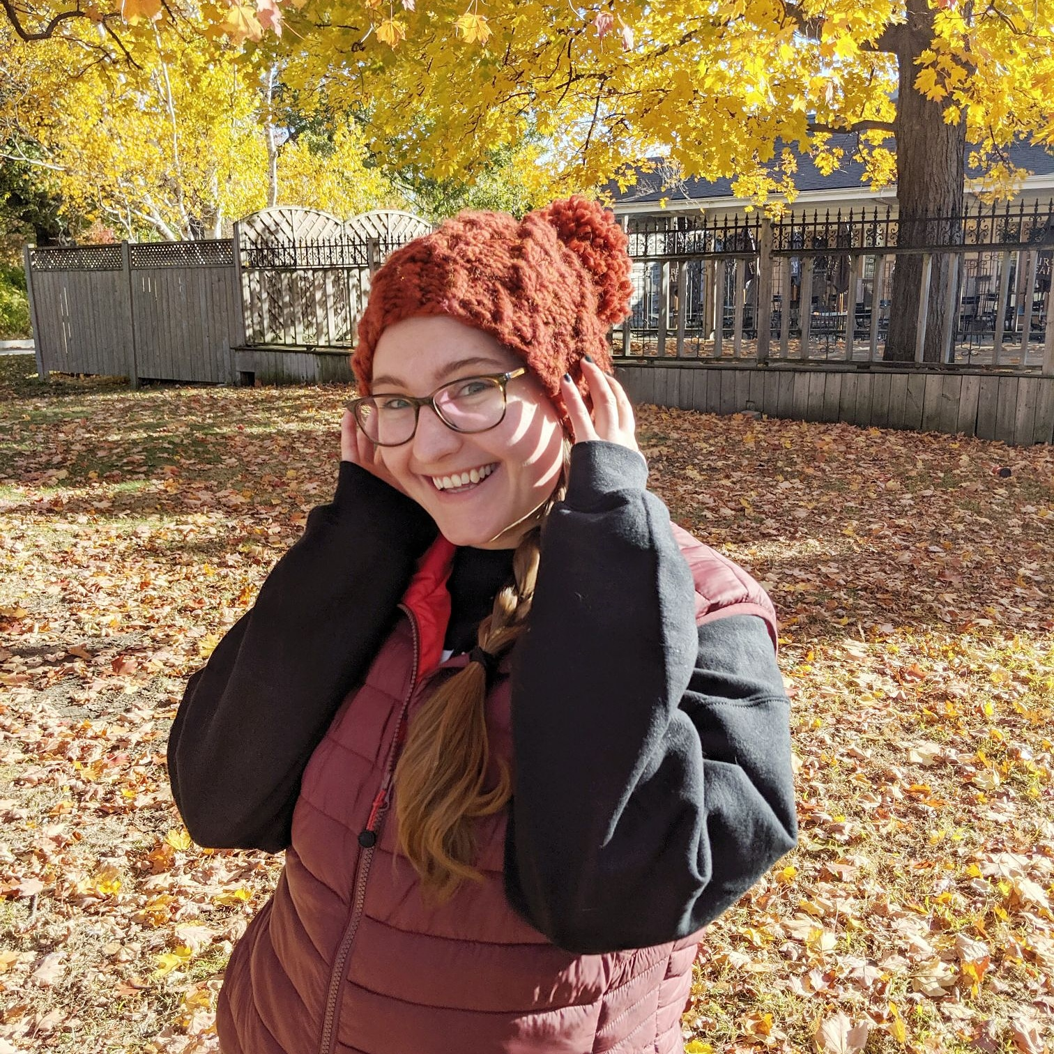 Young white woman wearing an orange knit hat poses in front of trees with yellow leaves