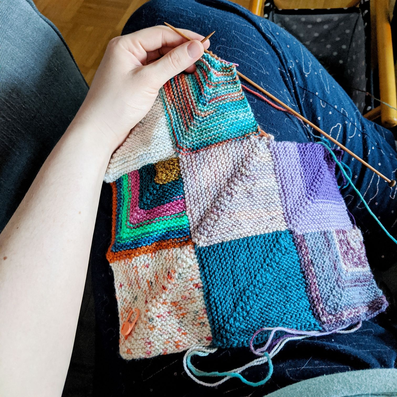 A Caucasian hand holds two knitting needles working on a patchwork blanket