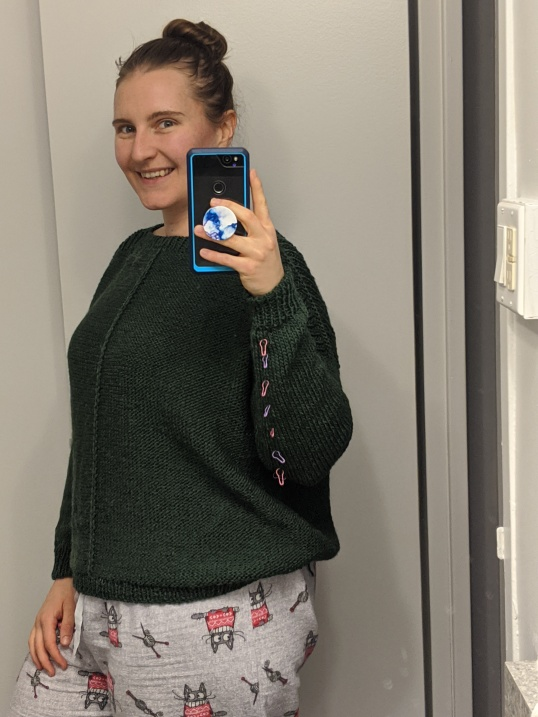 A young white female takes a selfie in the mirror wearing a green knit sweater