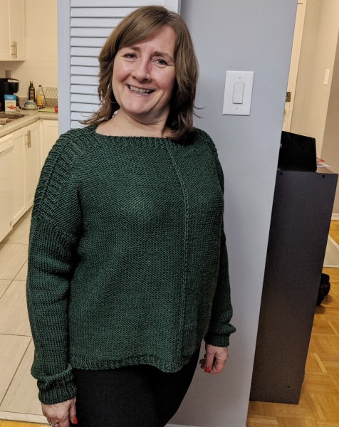 A white woman stands against a grey wall wearing a green knit sweater