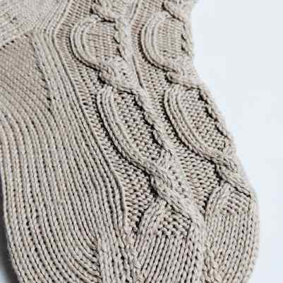 Hand knit socks with an intricate cable in beige yarn