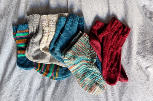 6 pairs of hand knit socks of different colours laid out overlapping on a bedspread.