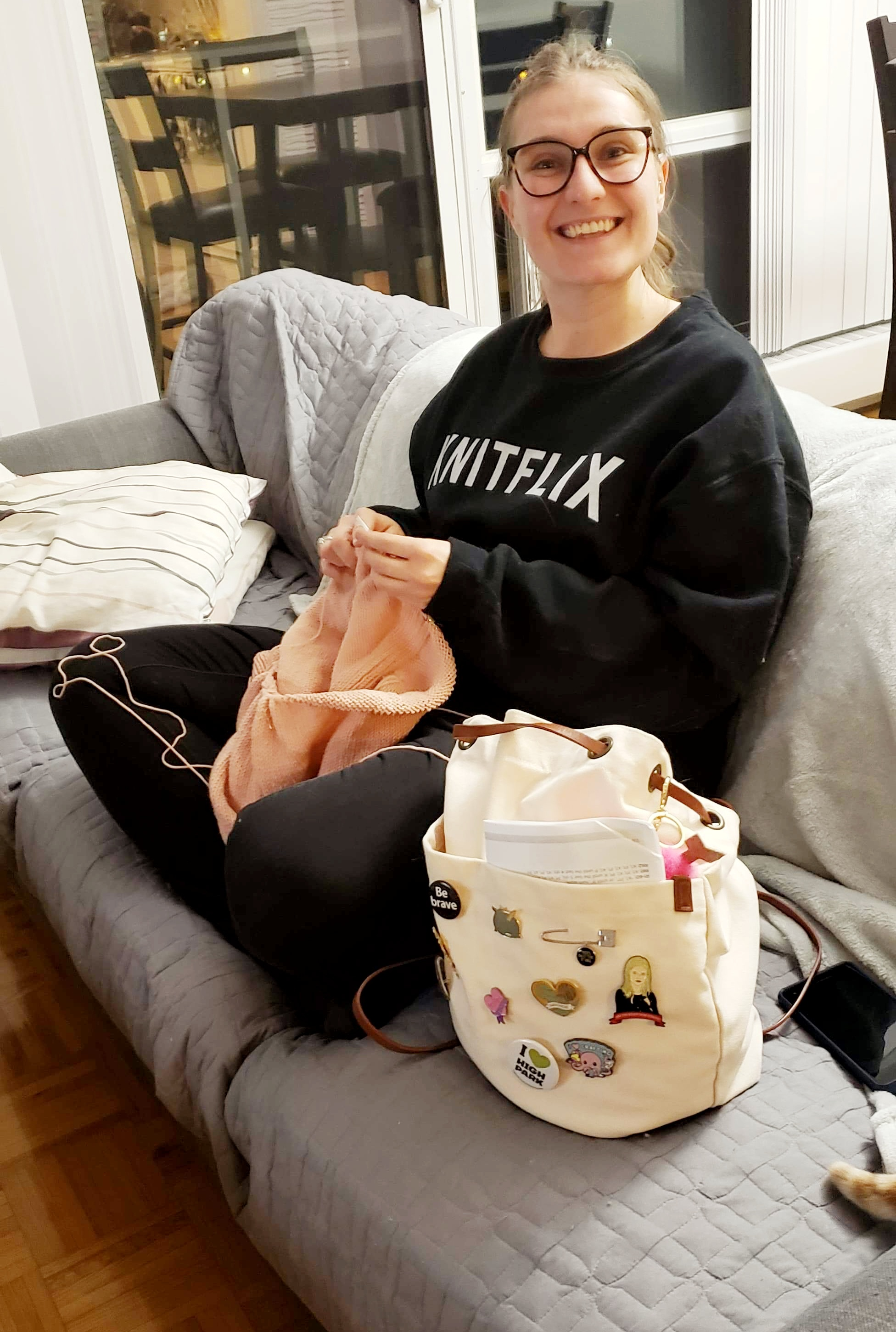 Young Caucasian woman sits on a grey couch knitting a pink sweater smiling at the camera