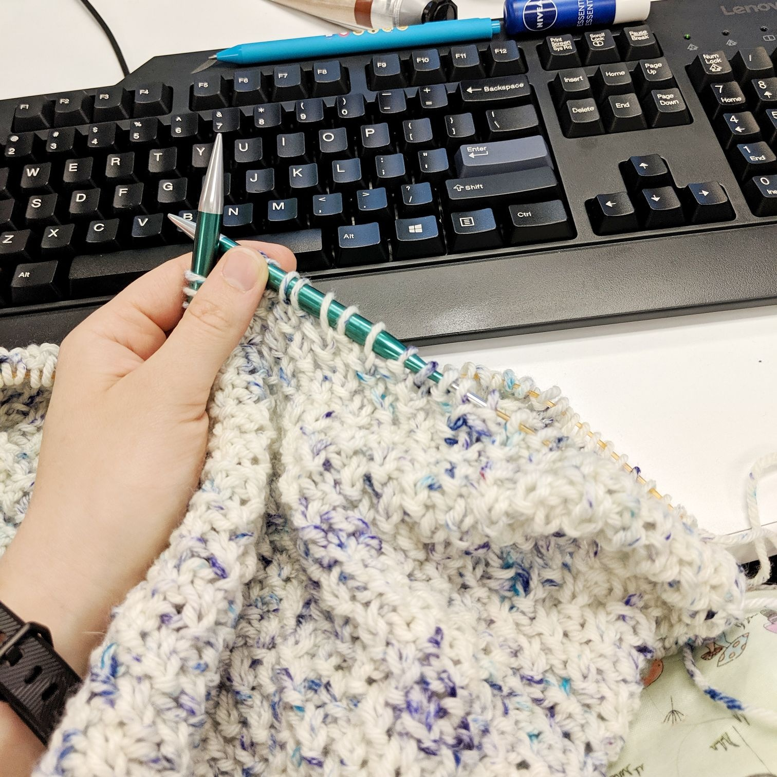 A white hand holds two knitting needles with white and blue knitting hanging off, on top of a white desk, a keyboard is in the background