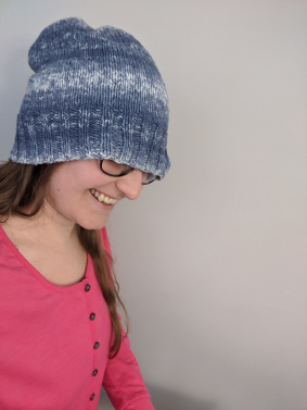 A young white woman wears a stretched out knit hat pulled over half her face