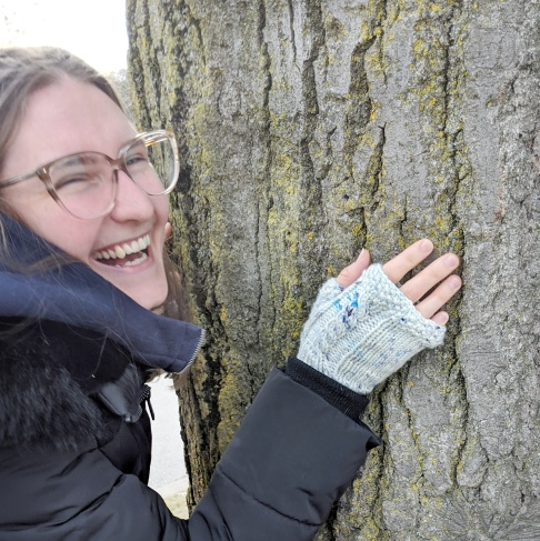 A young while woman wearing glasses leans with her hand against a tree trunk, she is wearing knit fingerless mitts.