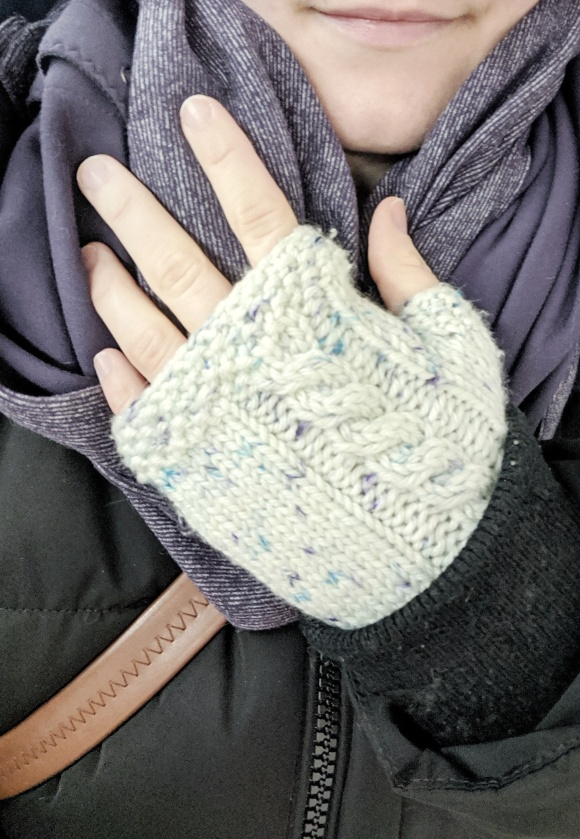 A white woman holds her hand on her chest showing knit fingerless mitts