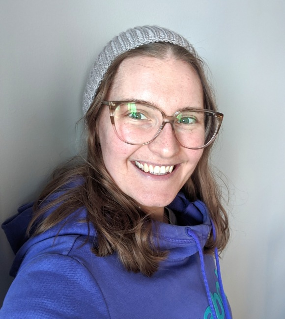 A young white woman wearing glasses and a grey knit hat smiles at the camera