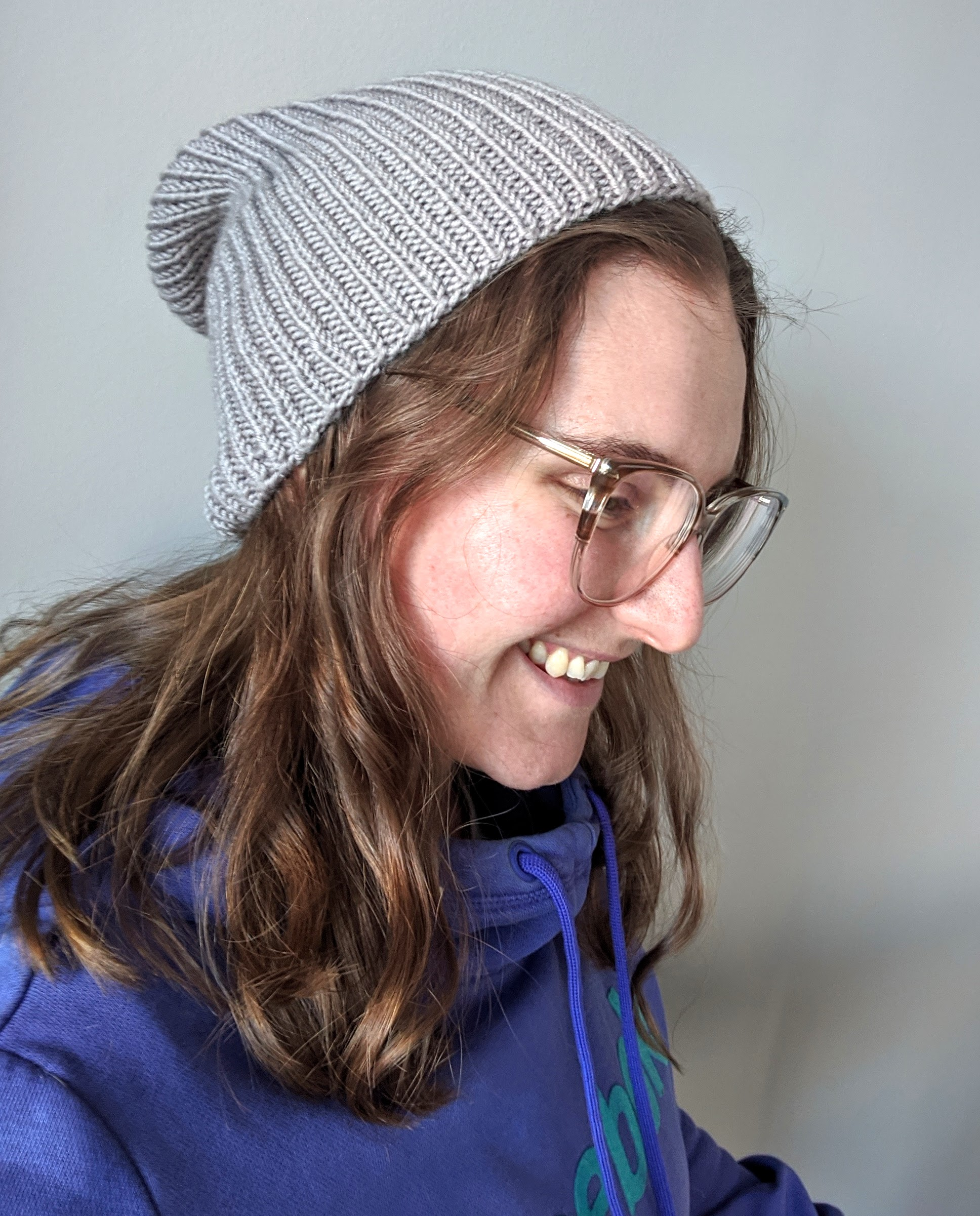 A young white woman with glasses on wears a great ribbed knit hat