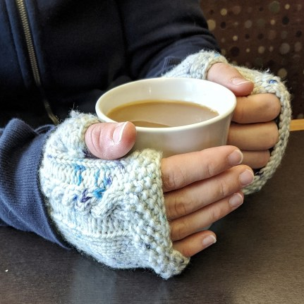 Two hands wearing blue speckled knit fingerless mitts hold a mug of coffee