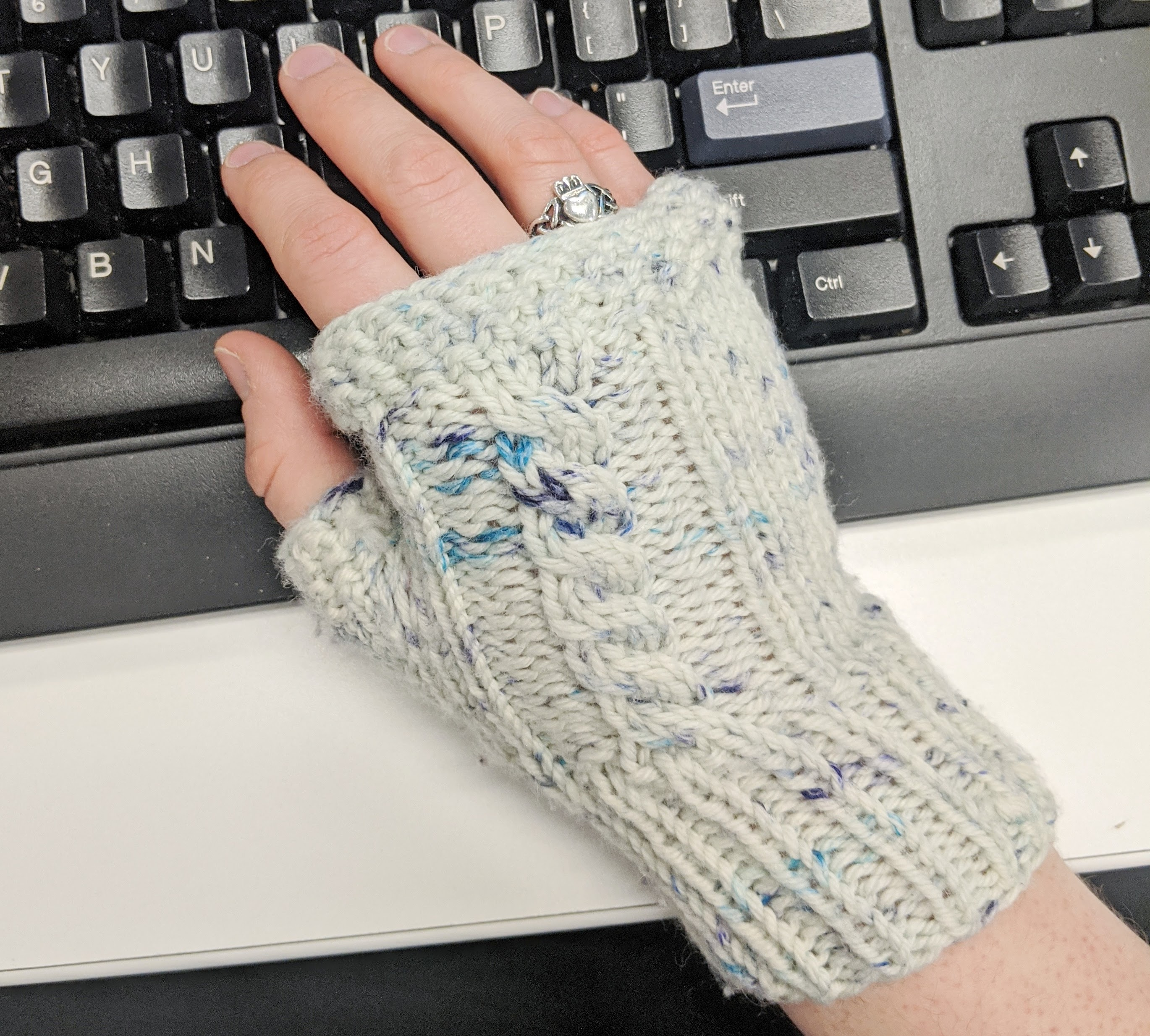 A white woman's hand lays on a computer keyboard wearing a knit fingerless glove