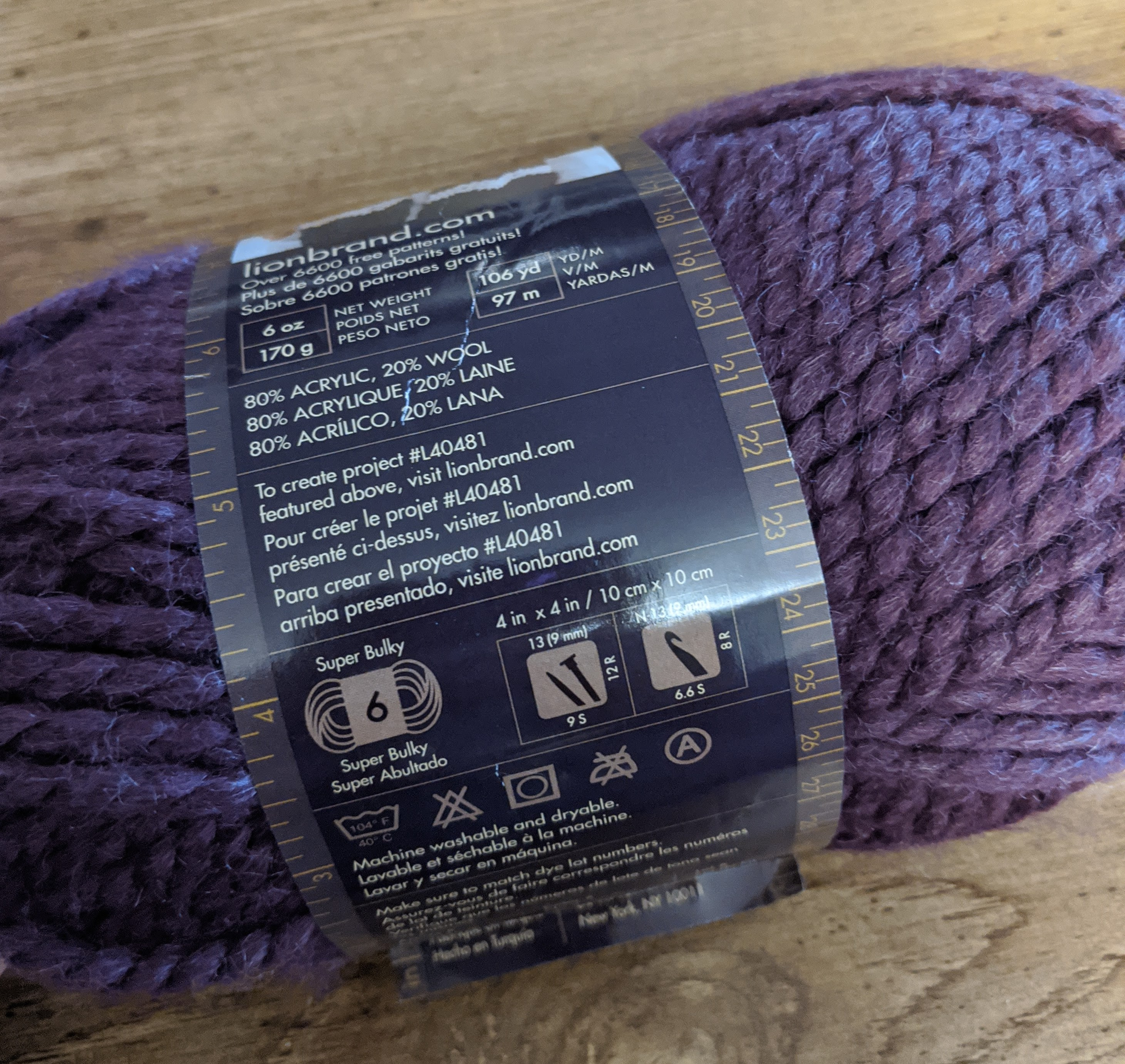 A dark purple ball of yarn on a wood table