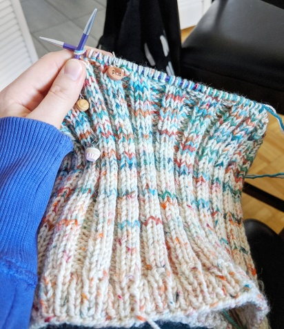 A hand holds two knitting needles with a blue, white and orange knitting piece on them