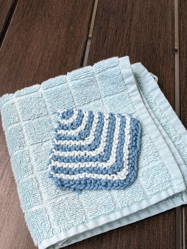 A reusable cotton scrubby sits on an aqua washcloth on a dark wood table