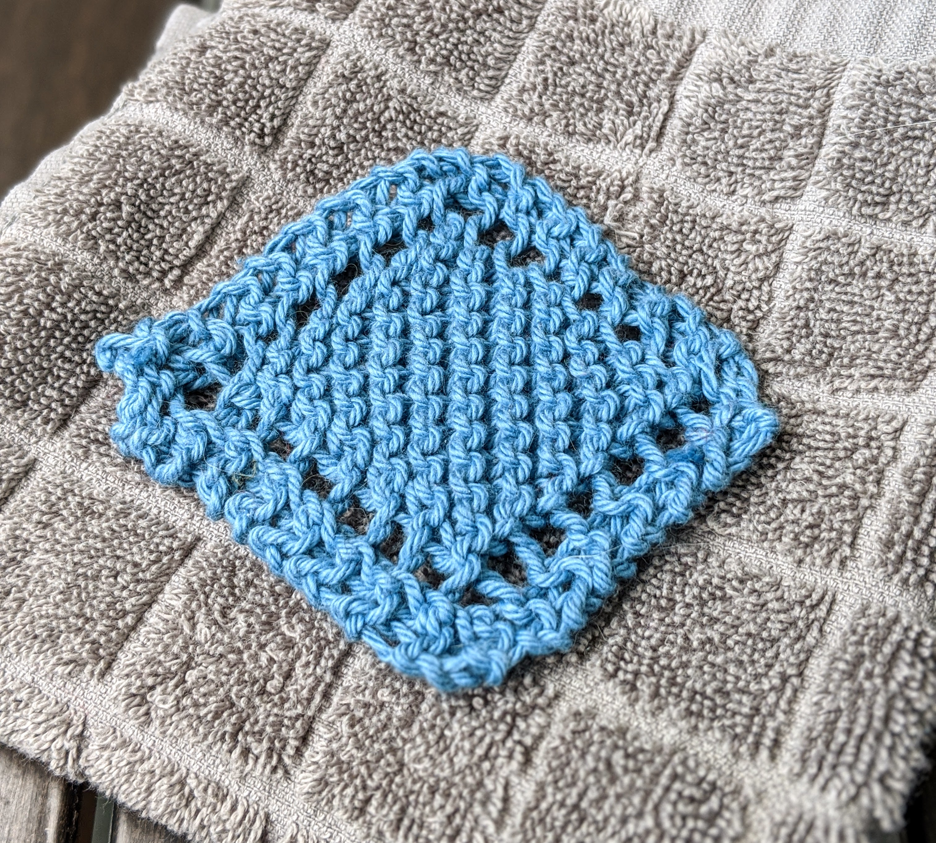A blue reusable cotton face scrubby sits on a grey washcloth