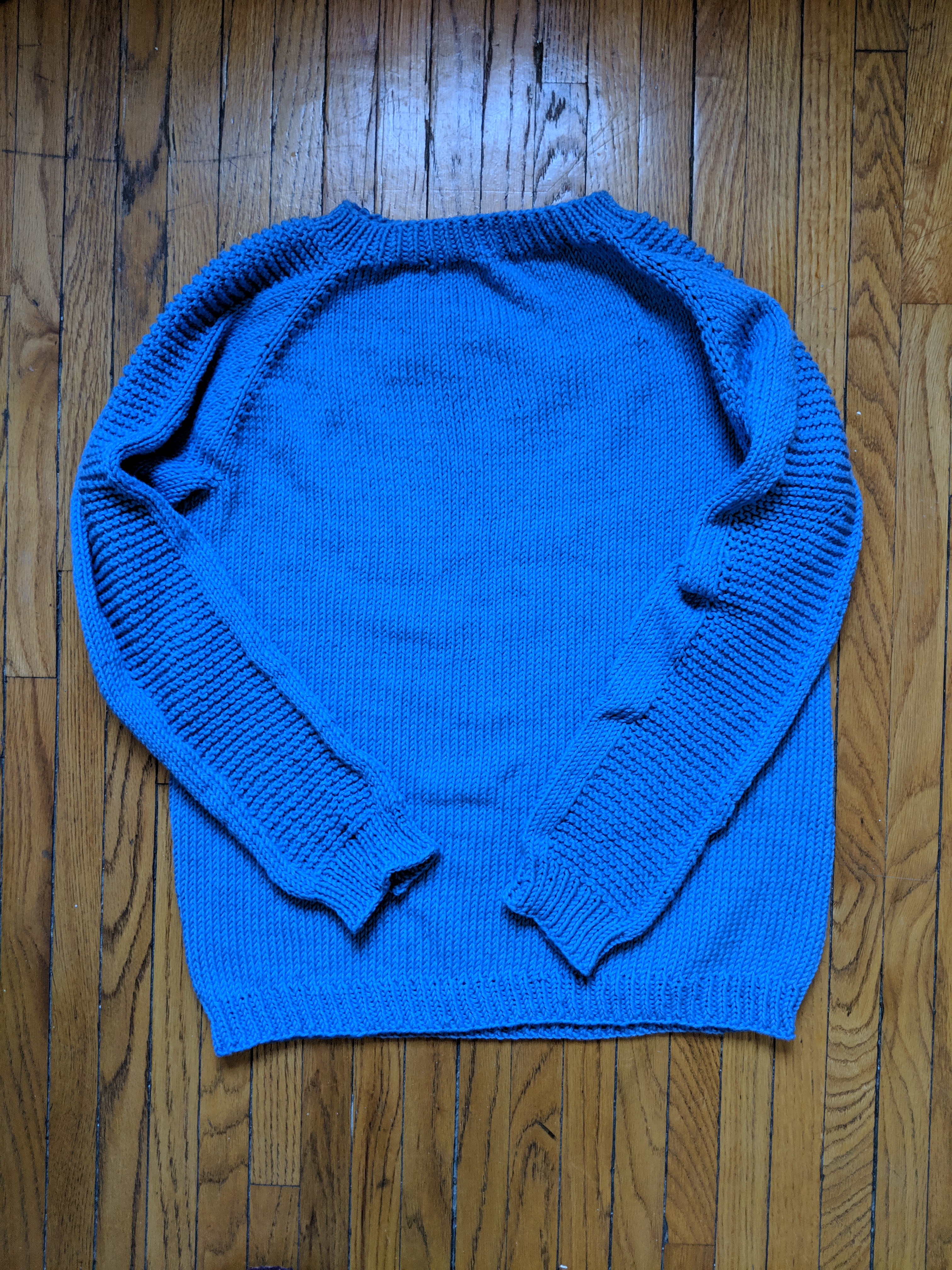 A blue knit Flax sweater lies spread out on a hardwood floor