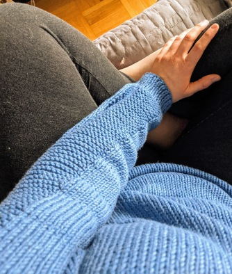 A picture taken from above of a white woman sitting cross legged, her torso, left arm and legs are visible. She is wearing a blue knit Flax sweater and grey leggings