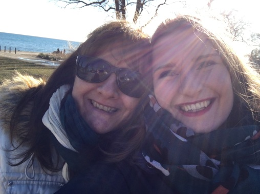 Mother and daughter smile at the camera, wearing Winter jackets and scarves,