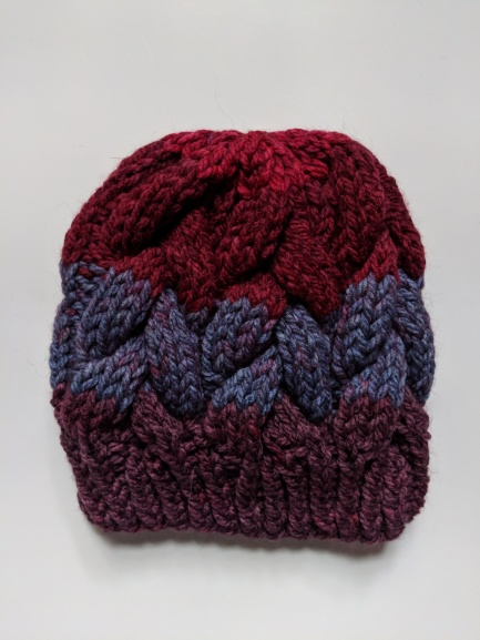 A knit striped hat in red and purple tones on a white background