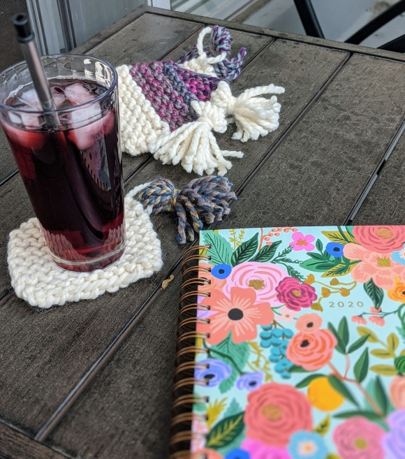 A floral 2020 Agenda book sits on a brown outdoor table with a glass of pink iced tea on a white hand knit coaster