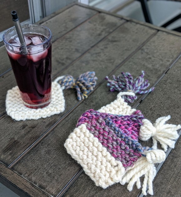 A glass of pink iced tea on a knit coaster, three other coasters are stacked next to it